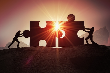 Teamwork, partnership and cooperation concept. Silhouettes of two businessman joining two pieces of puzzle together. Stock Photo