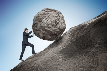 Sisyphus metaphore. Young businessman pushing heavy stone boulder up on hill.