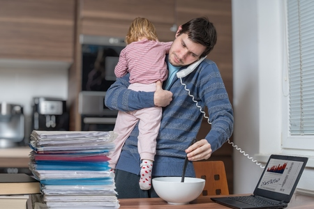 Multitasking father is babysitting and working at home. Foto de archivo