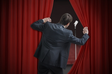 Nervous man is afraid of public speech and is hiding behind curtain. Stock Photo
