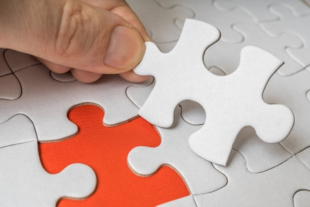 Hand of a man is connecting one last piece of white empty puzzle.