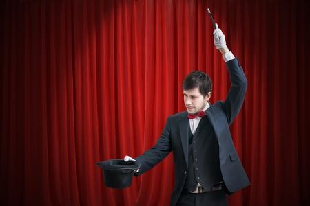Feliz mago o ilusionista está mostrando truco de magia con su varita. Cortinas rojas en el fondo.