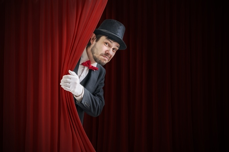 Nervous actor or illusionist is hiding behind red curtain in theater. Standard-Bild