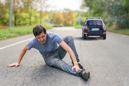 Hit and run concept. Injured man on road in front of a car. Фото со стока