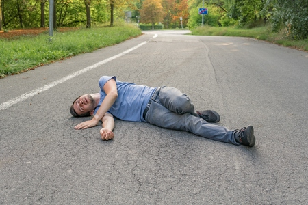 Injured man had an accident and is lying on road.