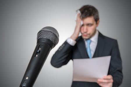 Nervous man is afraid of public speech and sweating. Microphone in front. 免版税图像 - 97073912