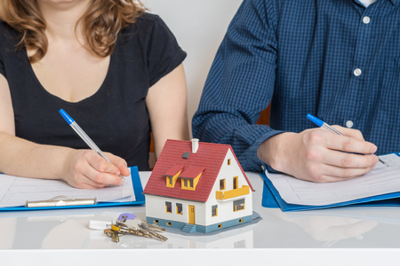 Divorce and dividing a property concept. Man and woman are signing divorce agreement. 스톡 콘텐츠