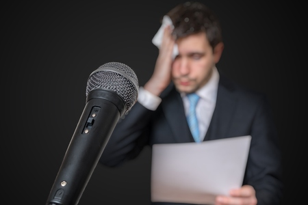 Microphone in front of a nervous man who is afraid of public speech and sweating. Archivio Fotografico