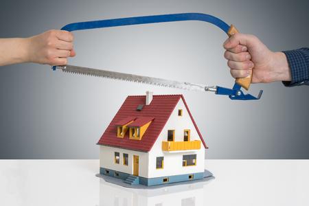 Divorciarse y dividir un concepto de casa. El hombre y la mujer están dividiendo el modelo de casa con sierra. Foto de archivo