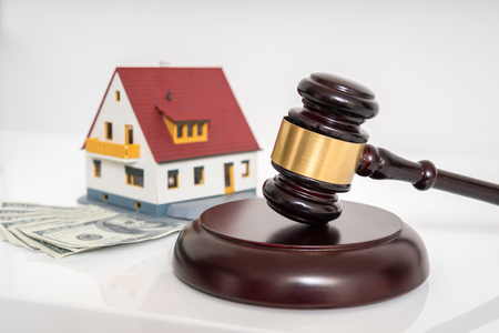 House auction concept. Gavel in front of model of house.