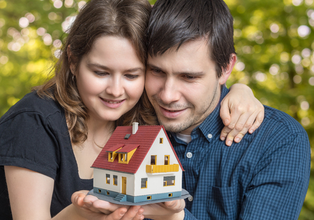 Young happy couple in love is dreaming and planning a new house.