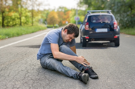 Hit and run concept. Injured man on road in front of a car. Stockfoto