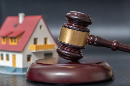 House auction concept. Gavel in front of a house model. Stock Photo