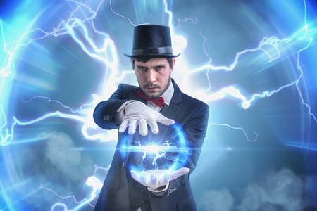 Magician or illusionist holds electric plasma ball radiating bright light. Lightning in background.
