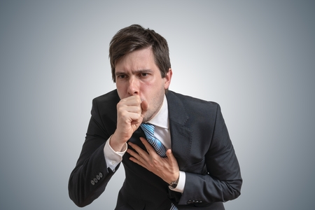 Young sick businessman is coughing. Stock Photo
