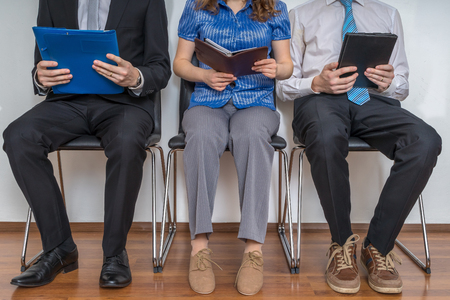 Group of people waiting for interview in a waiting room. Imagens