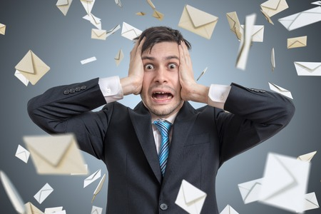 Frustrated young man and many falling envelopes. Many e-mails and spam concept.