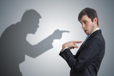 Schatten des Menschen zeigt und beschuldigt den Geschäftsmann. Gewissen Konzept.