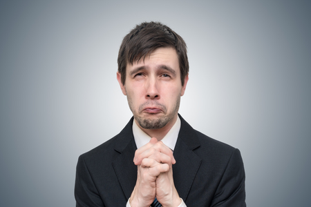 Funny young businessman is begging or asking for help.