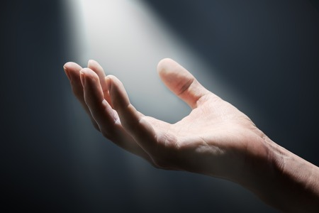 Bright light rays shihing on mans hand in darkness.