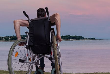 Young man is sitting on wheelchair near sea at sunset.