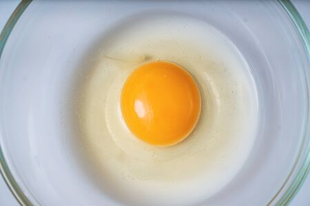 Raw uncooked egg in bowl. Yolk in center. Flat view from above. Stockfoto