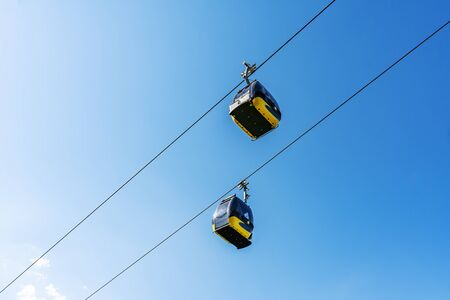 Cable car cabins liftng up on mountain against blue sky. Фото со стока