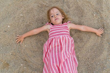 Little happy girl is lying on sandy beach at summer. Фото со стока