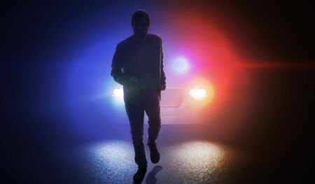Silhouette of man running away from police car at night.