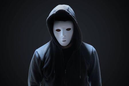 Masked anonymous hacker on black background. Stock fotó