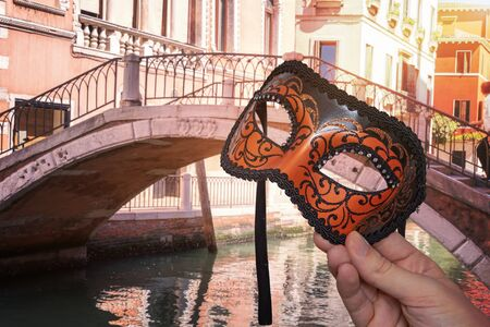 Hand is holding Venetian carnival mask at famous traditional venetian festival in Italy. Bridge over canal  in background.