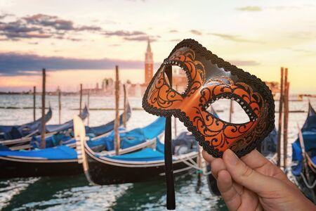 Hand holding Venetian carnival mask at traditional venetian festival in Italy. Gondolas in background.