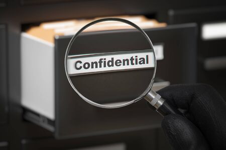 Man with magnifying glass looking on confidential secret files.