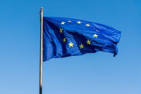 Flag of European Union (EU) against blue sky.
