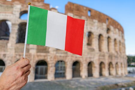 Man is holding italian flag in hand. Colosseum in background. Travel in italy concept. Zdjęcie Seryjne