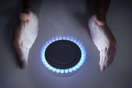 Man is warming hands near blue propane butane gas on stove.