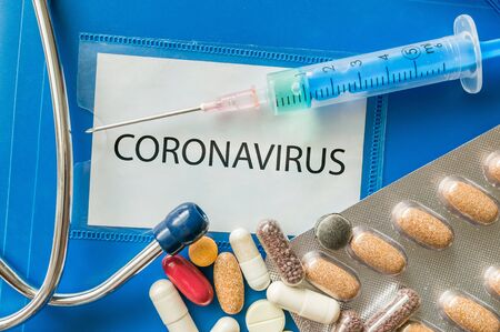 Novel coronavirus disease 2019-nCoV written on blue folder. Many pills, syringe and stethoscope.