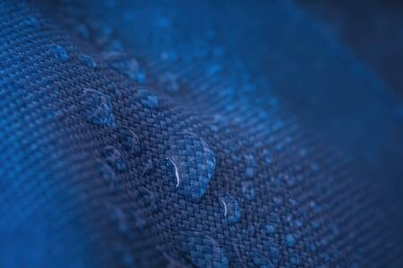 Water drops on waterproof impregnated blue fabric.