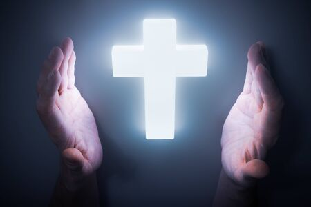 Man hands around shining light from glowing crucifix. Religion concept.