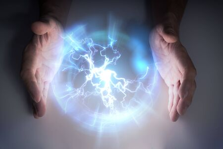 Plasma ball with lightning in hands of magician or illusionist. Stock Photo