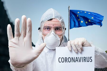 Doctor in coveralls warns of coronavirus infection in EU. European Union flag in background.