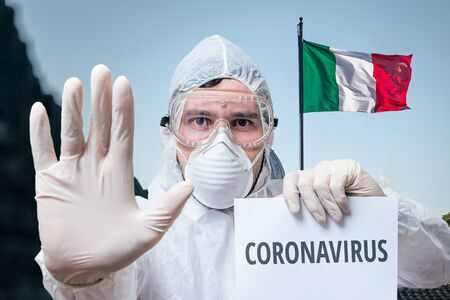 Doctor in coveralls warns of coronavirus infection in Italy. Italian flag in background.