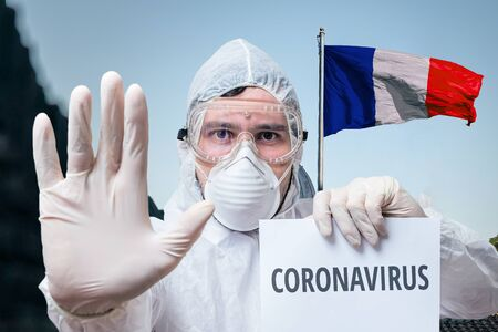 Doctor in coveralls warns of coronavirus infection in France. French flag in background.