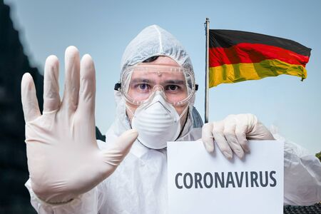 Doctor in coveralls warns of coronavirus infection in Germany. German flag in background.