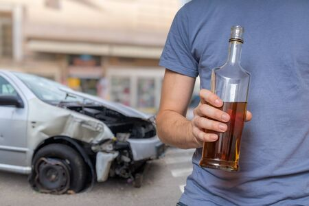 Traffic accident and alcohol concept. Drunk driver is holding bottle with alcohol in hand. Crashed car in background. Zdjęcie Seryjne