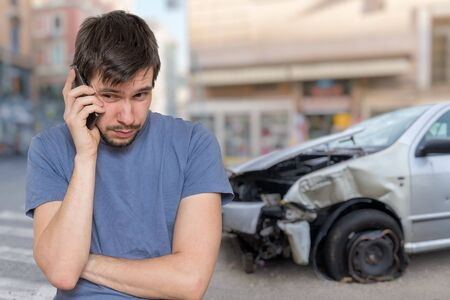 Sad man is calling to assistance after car accident. Zdjęcie Seryjne