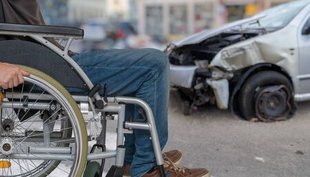 Disabled man on wheelchair had car accident. Crashed car in background. Zdjęcie Seryjne