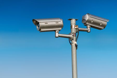 Security CCTV video camera against blue sky. 스톡 콘텐츠