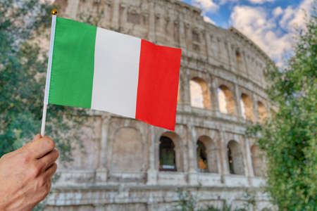 Man is holding italian flag in hand. Colosseum in background. Travel in italy concept. Zdjęcie Seryjne - 152330731