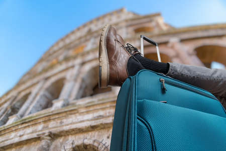 Young man is relaxing in Rome and has legs on suitcase. Colosseum in background. Stock Photo